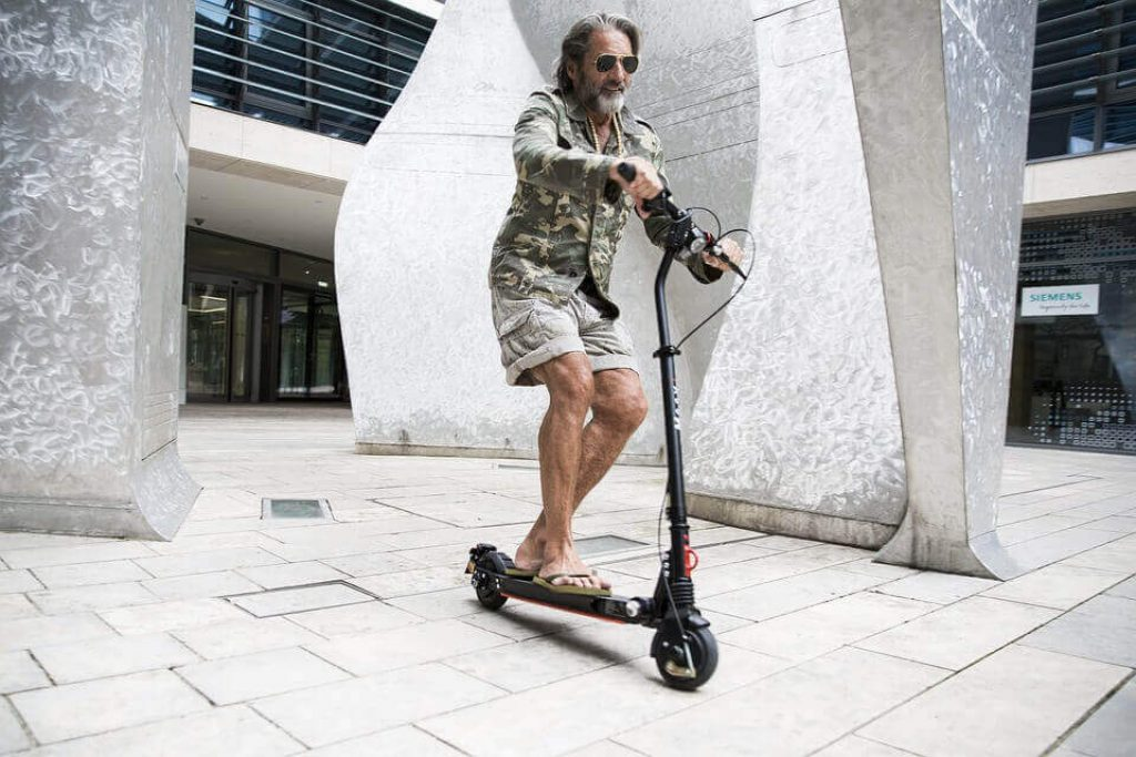 middle aged guy riding a scooter